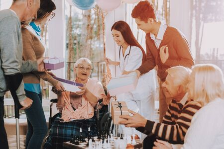 Birthday Party Celebration. Madly Happy Retiree. Nursing Home. Madly Happy Retiree in Wheelchair. Guests Give Gifts to Elderly Woman. Very Happy Young and Old People. Standard-Bild