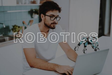Small Robot Stay on Table.  Busy Man Posing Focused. Small Mechanical Robot. Man Work in Kitchen.