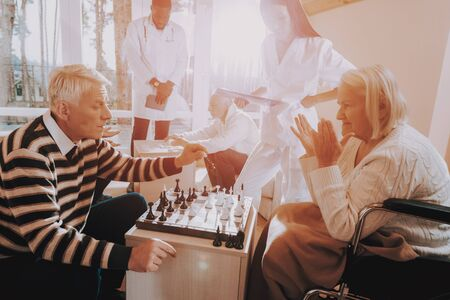 Elderly Couple Rehabilitation. Nursing Home. Senior Man and Woman Play Chess. Sitting Old Woman. Doctor and Nurse Stand Nearby. Patient on a Wheelchair.