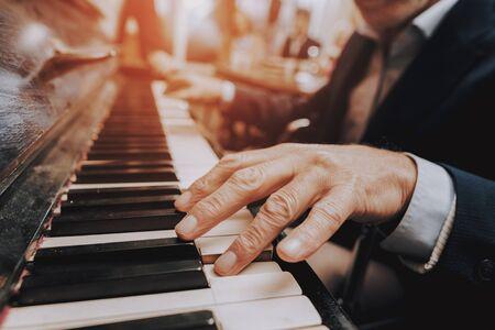 Männliche Finger auf Tasten. Älterer Mann spielt Klavier. Altenheim. Mann spielt Musik im Pflegeheim.