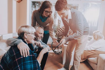 Nursing Home. Senior Couple Hold Lees of Life. Young People Visit Older. Sear and Yellow Leaf. Man and Woman Watch Something on Tablet. Standard-Bild