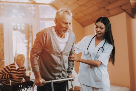 Woman Caregiver Old Bones. Medical Therapy. Adult Caucasian Hard Go Himself. Woman Supports Man. Asian Nurse Helps Adult Walker. Pensioner on Go-Carts. Nurse Hold Retired Person. Nursing Home. Stock Photo