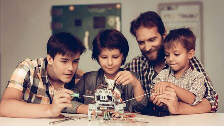 Bearded Father and Sons Constructing Robot at Home. Young Boy in Shirt. Indoor Joy. Modern Hobby Concept. Modern Technology. Robot Engineering Concept. Standard-Bild