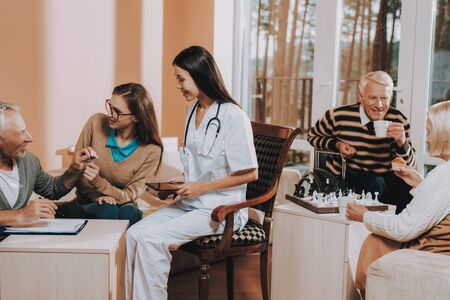 Old People Play Chess. Elderly Man Bequeaths House Keys. Sunshine Day in Nursing Home. Black-Haired Doctor Smiling. Retired Person Signs Contract.