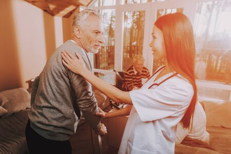 Asian Nurse Helps Adult Walker. Pensioner on Go-Carts. Adult Caucasian Hard Go Himself. Woman Caregiver Old Bones. Woman Supports Man. Medical Therapy. Фото со стока