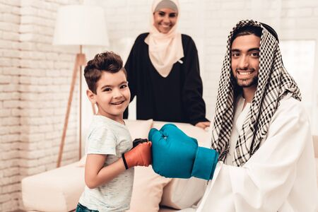 Arabian Boy Boxing with Young Father at Home. Healthy Lifestyle Concept. Hand in Gloves. Muslim Family. Smiling Boy at Home. Young Arabian Man. Sports Indoor. Father and Son. Indoor Fun.