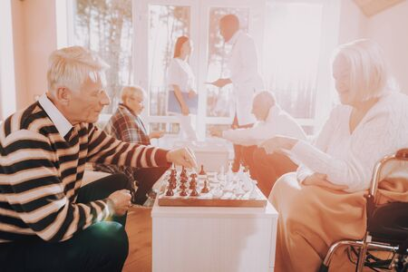 Senior Man and Woman Play Chess. Nursing Home. Doctor and Nurse Stand Nearby. Elderly Male Rehabilitation. Patient on a Wheelchair. Sitting Old Woman. Young and Old People in Nursing Home.