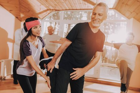 Active Retiree Nursing Home. Old Men do Exercises. Patient Wearing Sport Uniform. Young Instructor Show Exerscises. Elderly People Engaged. Therapeutic Gymnastics. Old People Healthcare Lifestyle.