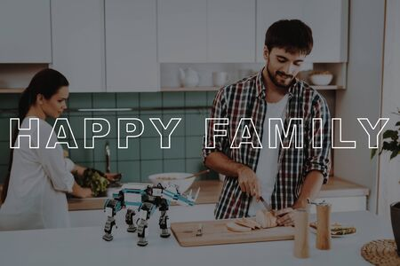 Small Robot in Front. Young Family Cooking. Busy Couple. Happy Family. Girl Smiling. Bubbly Relationships. Young Couple Sit in Kitchen. Guys Have Break. Family Leisure Time. 写真素材