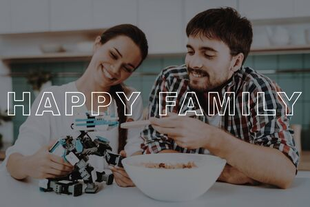 Man Feed Robot. Spoon with Salad. Girl Hold Robot. Bubbly Relationships. Happy Family. Young Couple Sit in Kitchen.