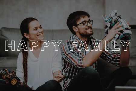Guy Hold Mechanical Robot. Girl Help Guy Create Robotics. Happy Family. Work Together.