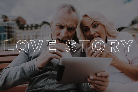 Old Couple Eat Burgers. Couple Love Story. Man Hold Tablet. Woman Smiling. Retired People Happy Together. Old Couple Bubbly Relationships. Two Pensioners Sit on Bench. Pensioners Spend Leisure Time.