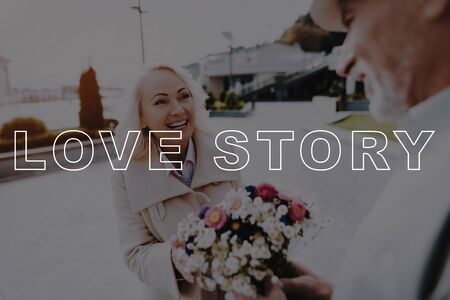 Elderly Man Gift Flowers to Woman. Couple Love Story. Old Couple Bubbly Relationships. Retired People Happy Together. Two Pensioners Stay in Park. Two Pensioners Spend Leisure Time.