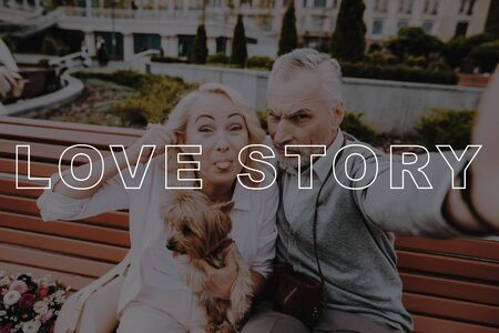 Two Pensioners with Little Dog. Pensioners Couple Selfie. Pensioners Rest in Park. Old Couple Bubbly Relationships. Couple Love Story. Old People on Date. Retired People Sit on Bench.