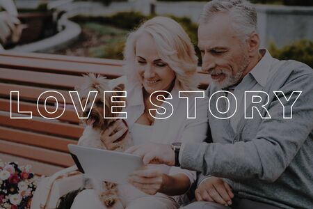 Woman Hold Little Dog. Old Couple Watch in Tablet. Couple Love Story. Old People Happy Together. Pensioners Bubbly Relationships. Couple Have Interesting Trip. Pensioners Sit on Bench. Standard-Bild