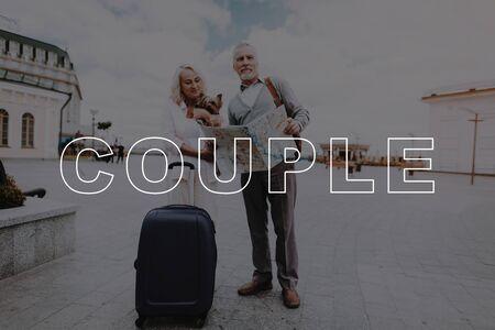 老夫婦はリトルドッグと一緒に旅行します。公園の2人の年金受給者。引退した人々の甘い瞬間。女性は小さな犬を保持します。引退した人々は一緒に幸せ。カップルラブストーリー。カップルバブリー関係。 写真素材