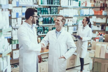 Pharmacists is Working. Two Men Handshaking with Each Other. Persons is Smiling. Woman Writing Information about a Medicine.