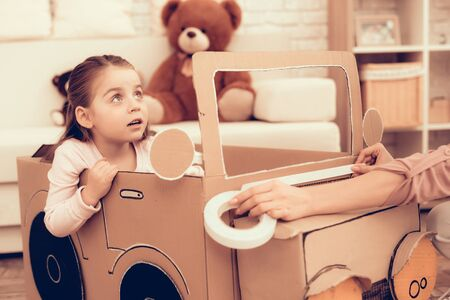 Girl Sitting in Cardboard Car. Child Development. Mom and Daughter Play. Happy Mom and Child Build Car. Woman and Daughter.