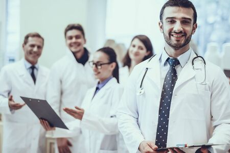 Male Pharmacist with Stethoscope Smiling. Man Looking into a Camera. Other Pharmacists Working on Background. Pharmacists is Wearing a Special Medical Uniform. Zdjęcie Seryjne