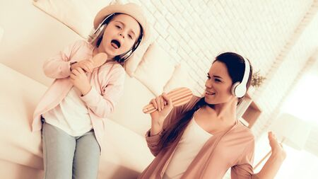 Mother Have Fun with Daughter. Kids Home Games. Learning at Home. Child Development. Mom and Daughter Sing. Girl in Headphones Dancing. Happy Mom and Child in Pajamas. Child with Comb in Hand Sings. Zdjęcie Seryjne