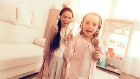 Mother Have Fun with Daughter. Kids Home Games. Learning at Home. Child Development. Mom and Daughter Sing. Girl in Headphones Dancing. Mom and Girl in Pajamas. Child with Comb in Hand Sings.