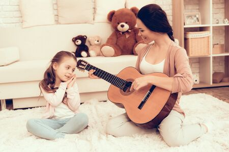 Kids Home Games. Rest at Home. Child Development. Mom and Daughter Play. Happy Mom and Child in Pajamas. Woman and Daughter. Play Guitar. Woman Playing Guitar. Mother Teaches Daughter. White Interior