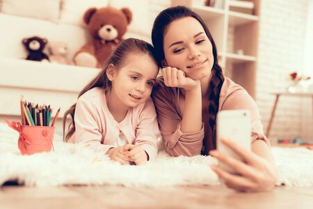 Fun with Daughter. Rest at Home. Child Development. Smiling Mom and Daughter. Happy Person in Pajamas. Girl and Mom Lie on Carpet. Colour Pencils. Smiling Mom and Daughter. Make Selfie. Phone in Hand.