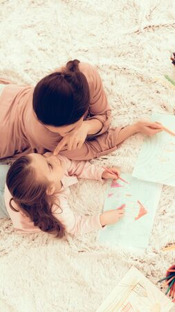 Mom Fun with Daughter. Kids Home Games. Rest at Home. Child Development. Mother and Daughter Play. Happy Mom and Child in Pajamas. Girl and Mother Lie on Carpet. Colour Pencils. Mom and Daughter Draw. Standard-Bild