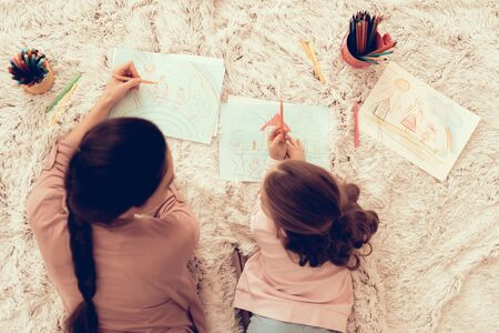 Fun with Daughter. Paper and Pensil. Rest at Home. Child Development. Mom and Daughter Play. Happy Mom and Child in Pajamas. Girl and Mother Lie on Carpet. Colour Pencils. Mom and Daughter Draw.