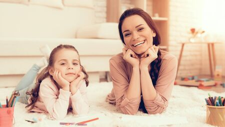 Mother Fun with Daughter. Rest at Home. Child Development. Mom and Daughter Play. Happy Mom and Child in Pajamas. Girl and Mother Lie on Carpet. Colour Pencils. Woman and Daughter Draw. White Interior