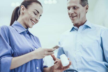 El hombre y la mujer eligen un medicamento. Hombre mirando a mujer sonriente. Mujer sosteniendo una botella con pastillas. Mujer mirando información sobre un medicamento en el teléfono móvil. Personas ubicadas en farmacia. Foto de archivo