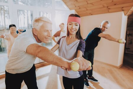 Old Men with Equipment. Patient Wearing Sport Uniform. Young Instructor Show Exercises. Imagens