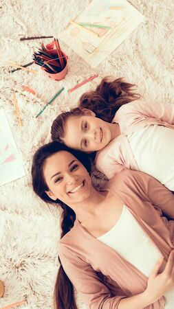 Woman Fun with Daughter. Rest at Home. Child Development. Mom and Daughter Play. Happy Mom and Child in Pajamas. Girl and Mother Lie on Carpet.