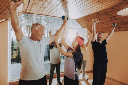 Patient Wearing Sport Uniform. Young Instructor Show Exerscises. Elderly People Engaged. Old Men with Equipment. Active Retiree Nursing Home. Therapeutic Gymnastics. Old People Healthcare Lifestyle. Standard-Bild