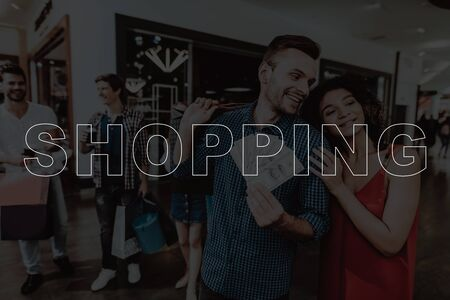 Young Couple Shopping At The Mall. Black Friday Sale. Holiday Discounts. Bags With Clothes. Happy Together. Stylish Teenagers. Rush Of Customers. Bunch Of Money. Point At The Showroom.