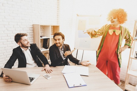 Young Man in Clown Costume on Meeting in Office. April Fools Day. Businessman in Office. April Jokes. Crazy Day. Workers on Meeting. Holidays and Celebration Concept. Clown with Red Nose.