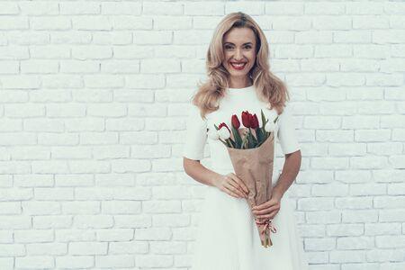 チューリップのブーケを持つ女性が部屋に立っています。白いドレス。赤いチューリップ。白い花。お祝いのコンセプト。