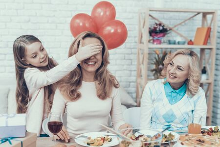 Family Preparing Surprize for Mother at Home. Cake on Table. Happy Family. Mother with Daugther. Smiling Women. Smiling Grandmother. Celebration Concept. Glass of Wine. Closed Eyes. Red Bbaloons. Stock Photo