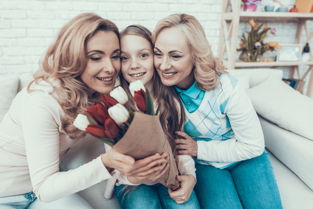Girl Presenting Bouquet of Tulips to Smiling Mother. Mother with Daughter. Smiling Women. Celebration Concept. Happy Family. Sitting at Home. Red Flower. White Flower. Holiday in March. Mothers Day. Stock Photo