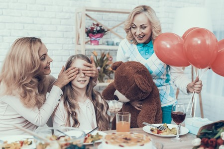 Family Preparing Surprize for Daughter at Home. Cake on Table. Happy Family. Mother with Daughter. Smiling Women. Smiling Grandmother. Celebration Concept. Toy Bear. Closed Eyes. Red Baloons.