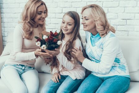 Mother Presents Bouquet of Tulips to Daughter. Mother with Daughter. Smiling Women. Celebration Concept. Happy Family. 写真素材 - 128610267