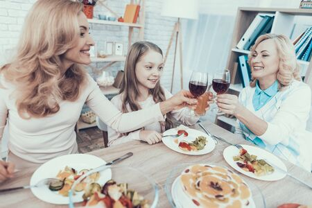 Happy Sitting Family Celebrating Birthday at Home. Cake on Table. Happy Family. Mother with Daughter. Smiling Women. Smiling Grandmother. Celebration Concept. Glass of Wine. Fruits on Plate.