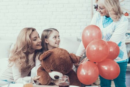 Grandmother Giving Toy Bear to Happy Girl at Home. Cake on Table. Happy Family. Mother with Daughter. 写真素材 - 128611356