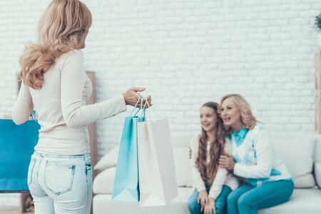 Mother Giving Packages with Gifts to Happy Family. Mother with Daughter. Smiling Women. Celebration Concept. Happy Family. 写真素材