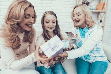 Babcia daje prezenty rodzinie w domu. Matka z córką. Uśmiechnięte kobiety. Koncepcja uroczystości. Szczęśliwa rodzina. Siedzieć w domu. Wakacje w marcu. Biała sofa. Szczęśliwa córka.