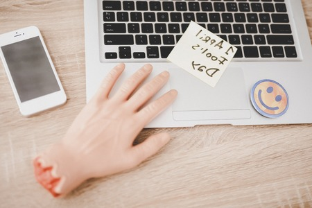 Fake Hand and Smiley Face near Laptop on Table. April Fools Day. April Jokes. Holidays and Celebration Concepts. Jokes in Office. Digital Device in Office. Laptop on Wooden Table. Rubber Hand. Stock Photo