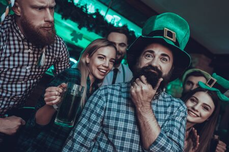 Saint Patrick's Day Party. Group of Friends is Celebrating. Happy People is Drinking a Green Beer. Friends is Young Men and Women. Man is Touching His Beard. People Wearing a Green Hats. Pub Interior.