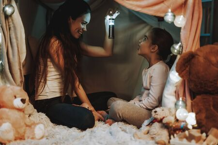 Mother and Daughter Lying on Carpet. Persons Lying Under the Fake Tent. Woman is Holding a Flashlight and Smiling. Girl Looking at Flashlight and Surprised. Evening Time. People in Home Interior. Foto de archivo