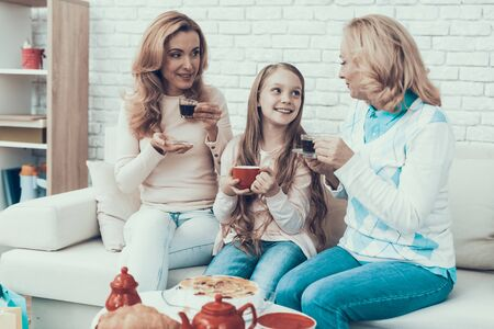Family Celebrating Birthday and Sitting at Home. Cake on Table. Happy Family. Mother with Daughter. Smiling Women at Home. Smiling Grandmother. Celebration Concept. Cup of Tea. Cup in Hand.