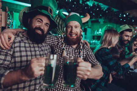 St. Patricks Day Party. Freunde feiern. Happy People trinkt ein grünes Bier. Freunde sind junge Männer und Frauen. Bartmänner stoßen miteinander an. Männer, die einen grünen Hut tragen. Pub-Interieur.